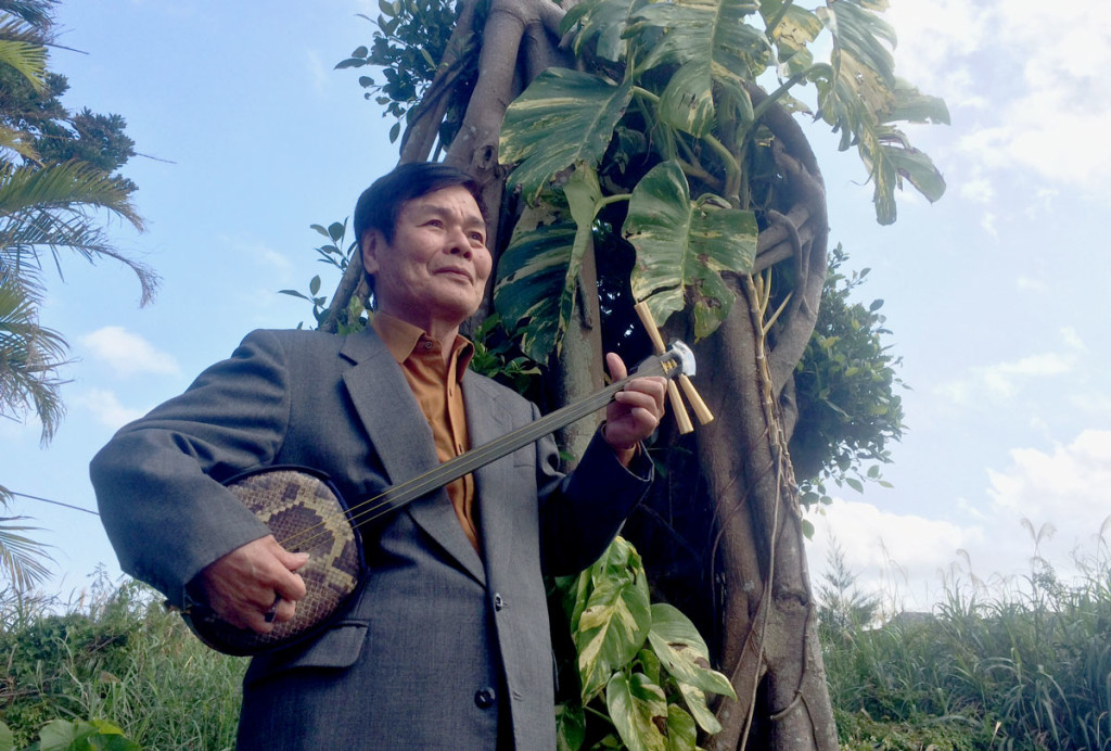 三味線を持ち木の前に立つ築地俊造