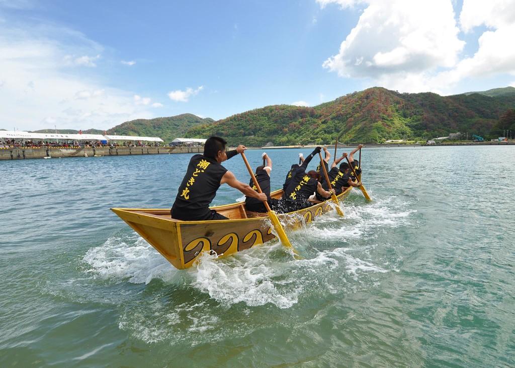 舟漕ぎ競争をする大人たち