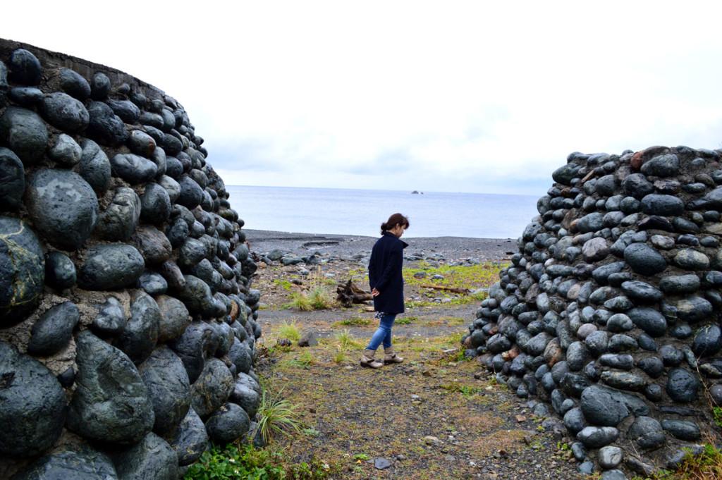 青久集落の玉石垣の間にいる女性