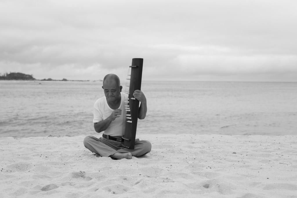 海辺で奄美竪琴を弾く盛島貴男