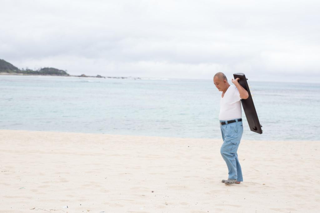 奄美竪琴を持って砂浜を歩く盛島貴男