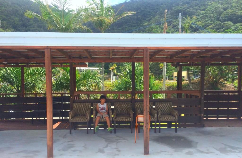 休憩所の椅子に座る少年
