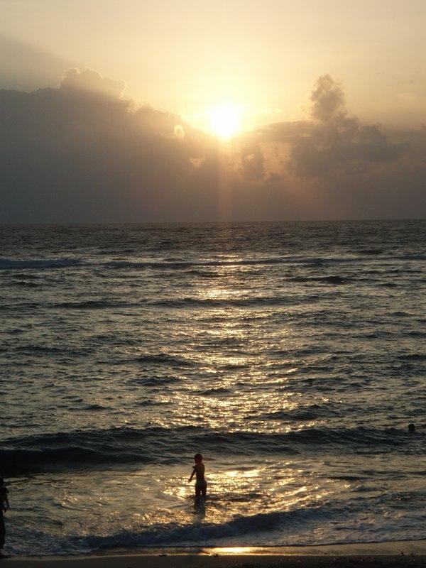 海で遊ぶ子供と夕日