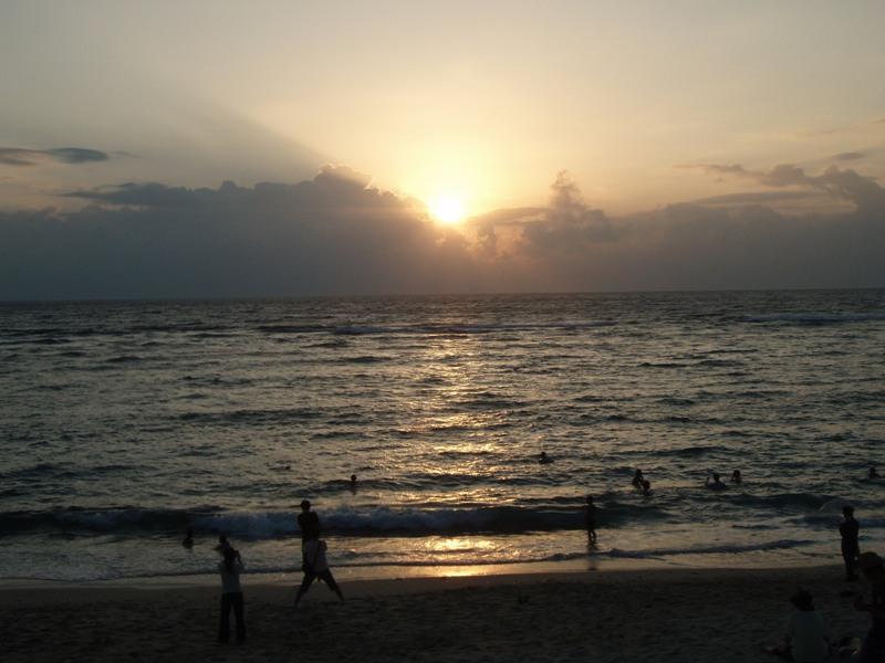 海水浴を楽しむ人々と夕日