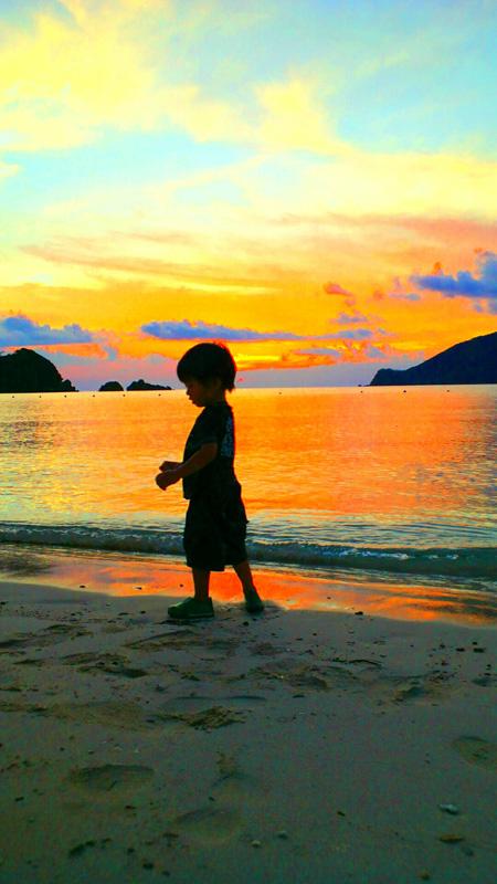 砂浜にいる子どもと夕日