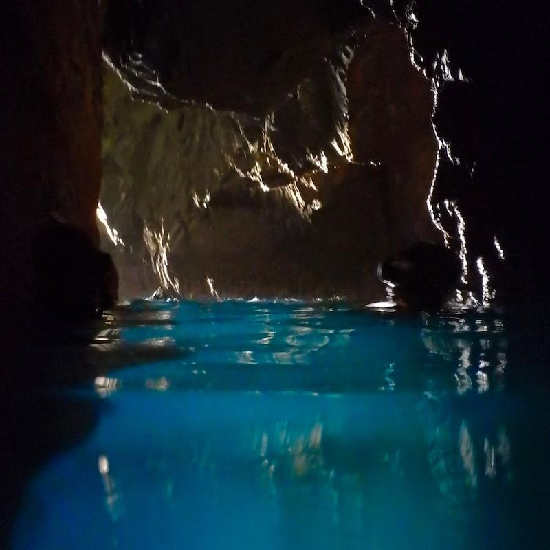 """船でしか行けない洞窟へ。海中が光を通して""""青の洞窟""""のようになっている。"""