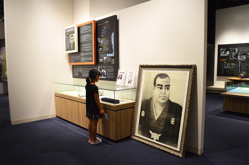 西郷の肖像画の前に立つ少女