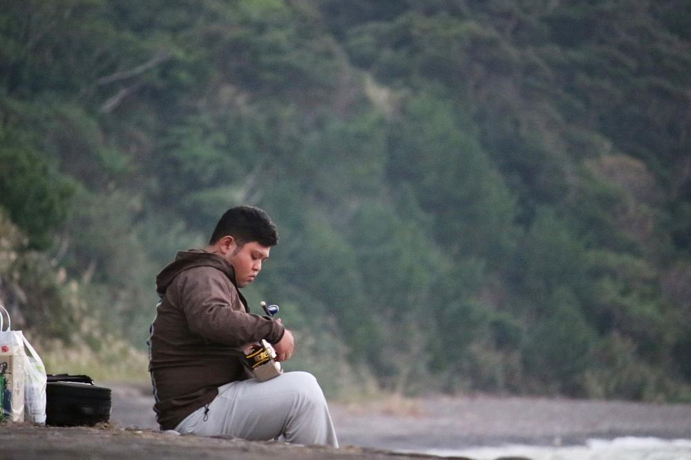 住用の海辺で三味線を鳴らす男性