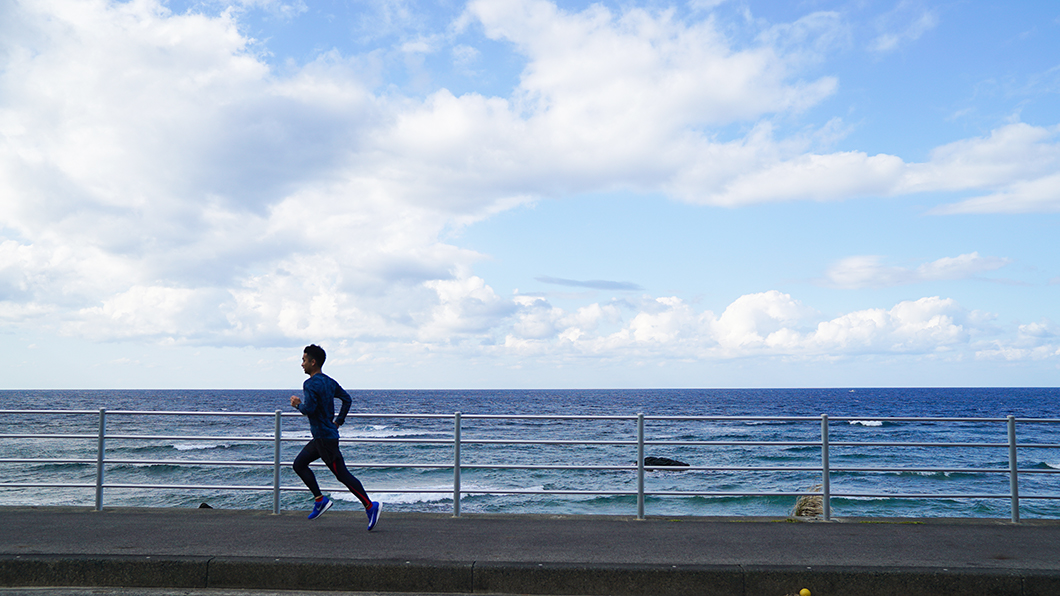 奄美市笠利海沿いを走る男性