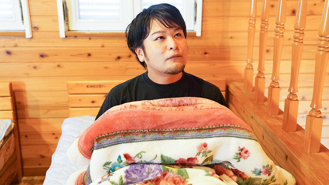 奄美市住用町のバンガローで寝る人