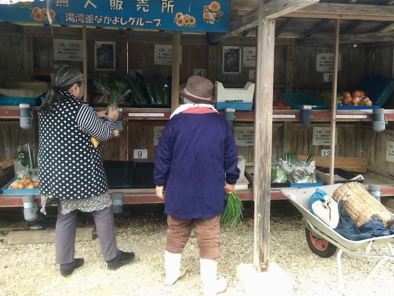 無人販売所に野菜を並べる人