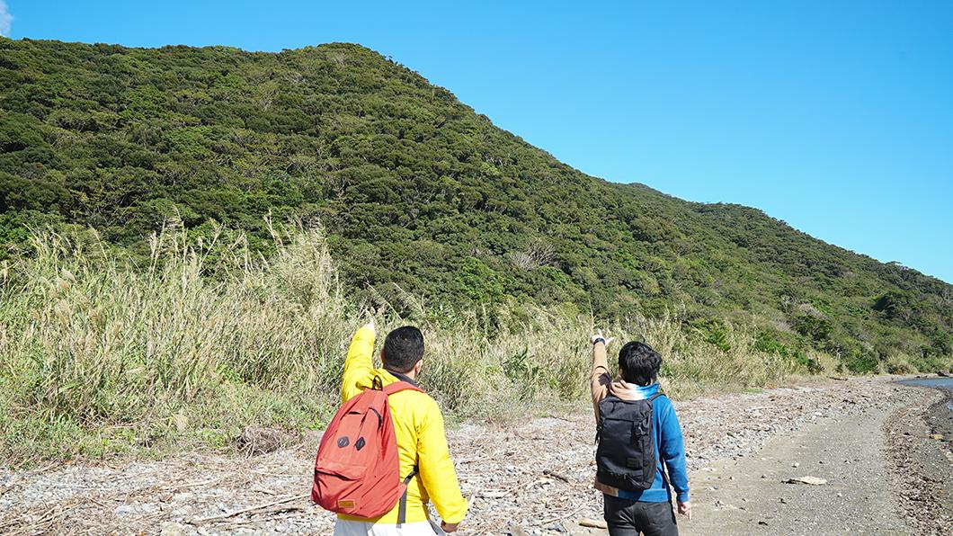 奄美市住用の山を指さす男の人