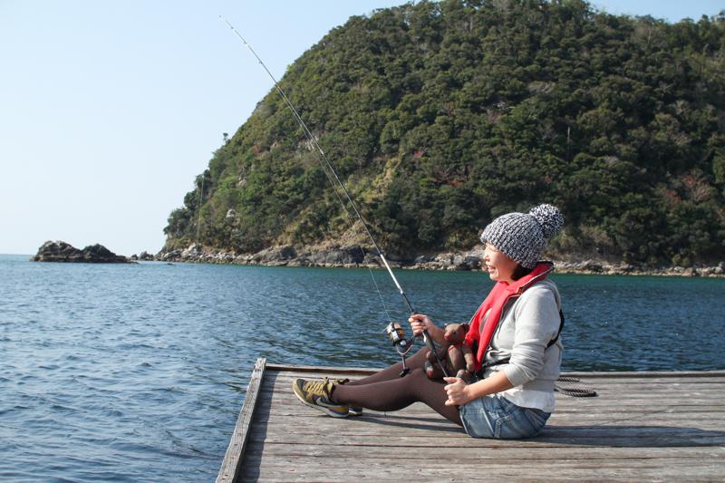 海に浮かぶ釣りイカダで釣りをする女性