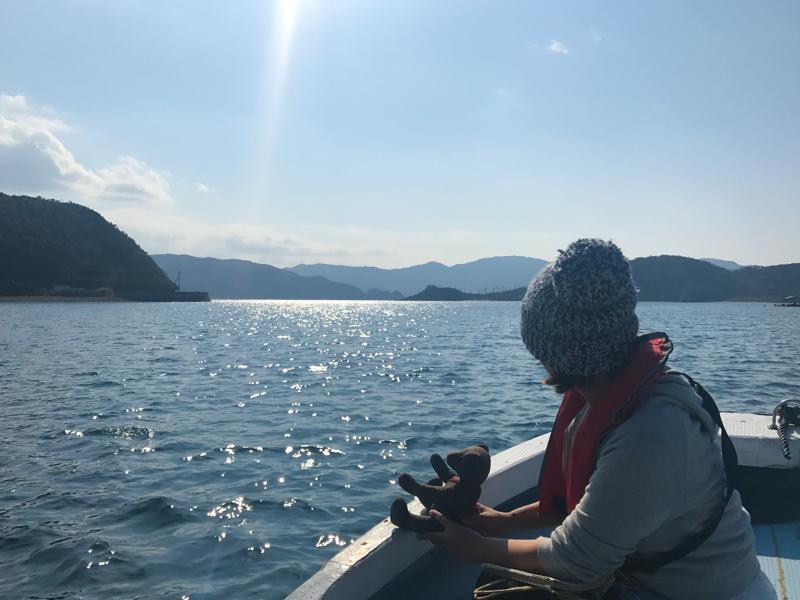 船に乗っている女性とくまのぬいぐるみ