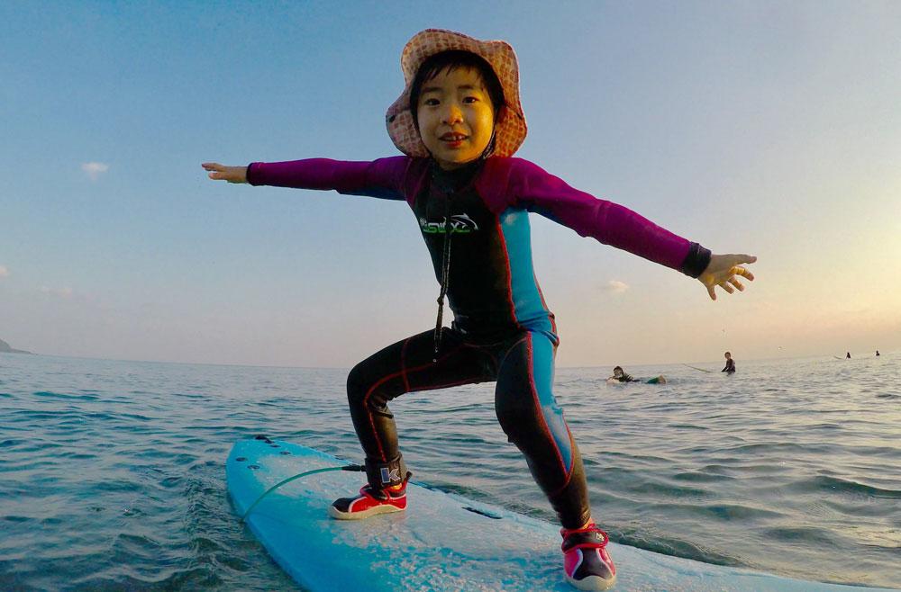 奄美でサーフィン体験する子ども:GREENHILL