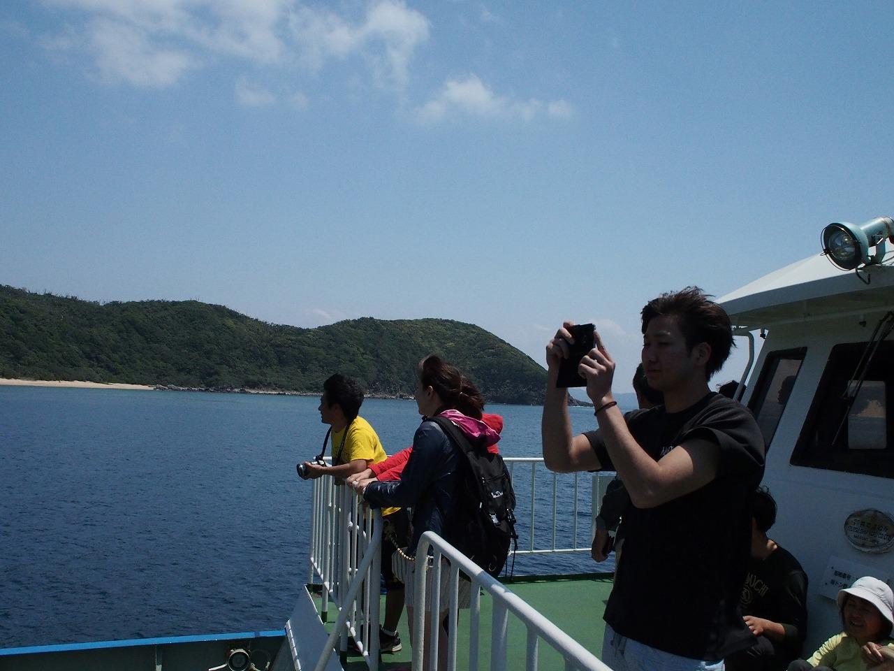 与路島に向かう船で写真を撮る男性