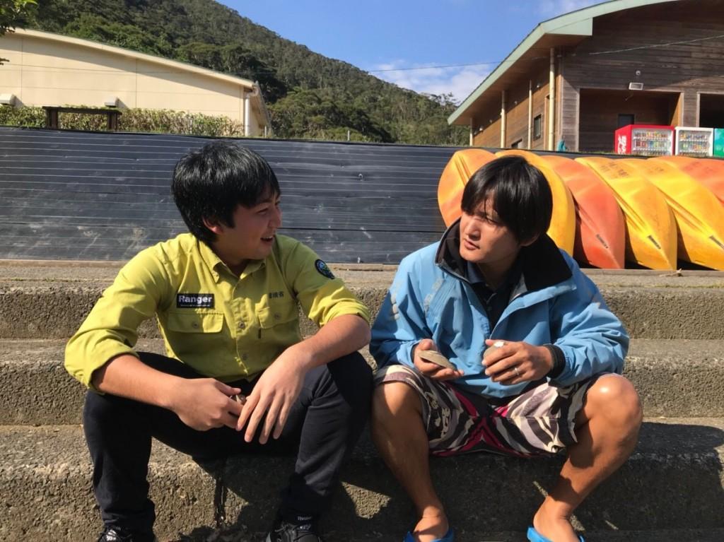 カヌー乗り場の前で座って話す男性二人