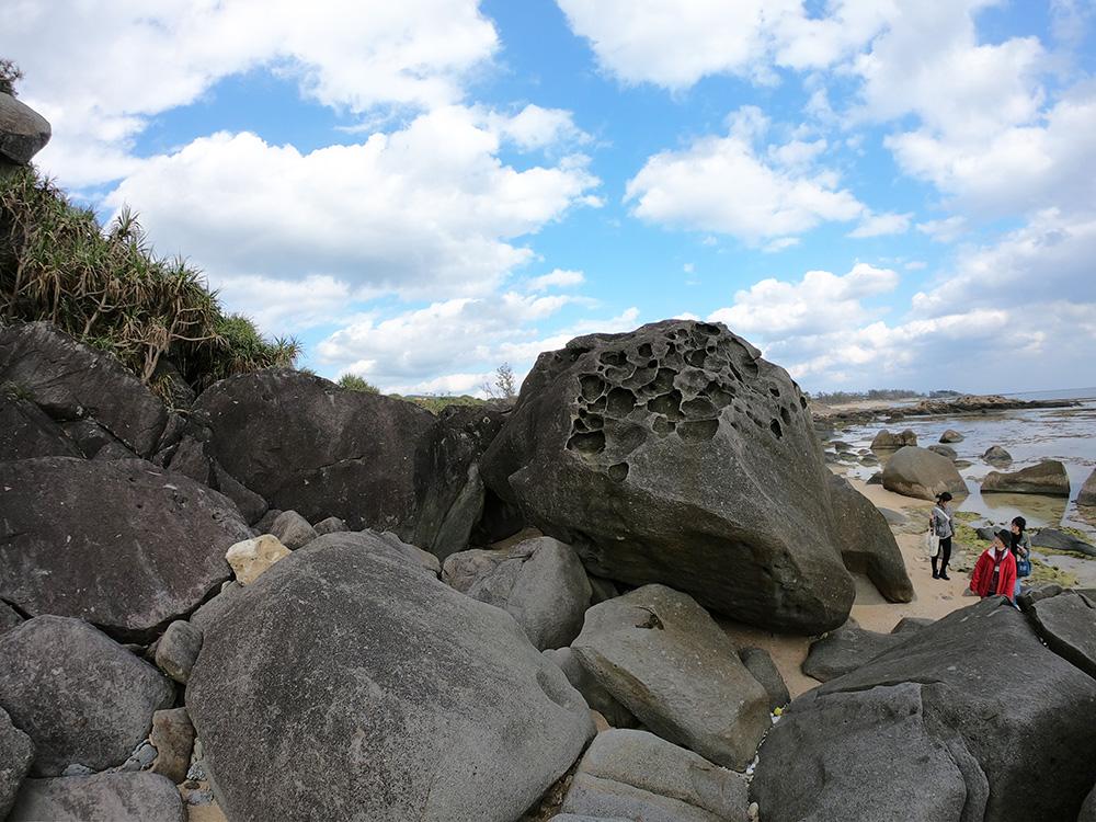 海岸の巨石を眺める女性