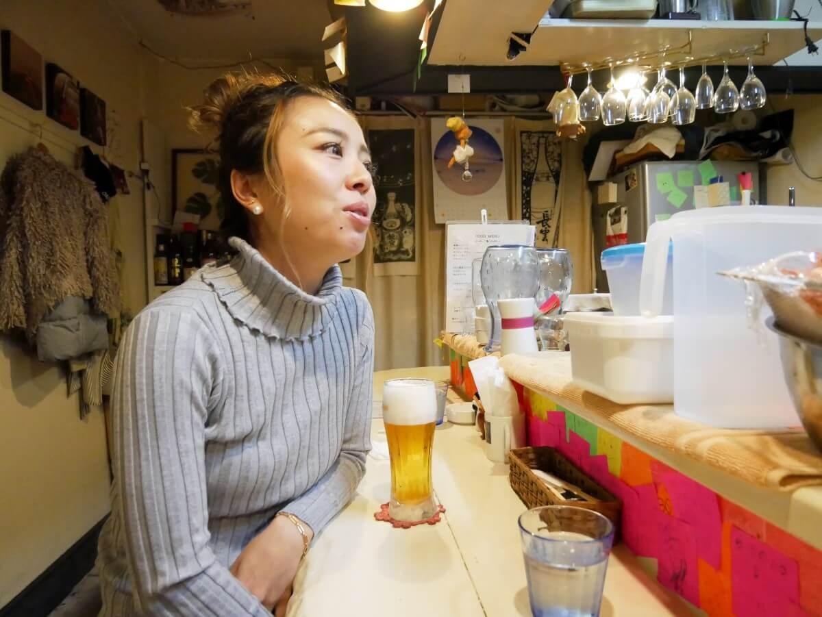 カウンターで生ビールを飲む女性