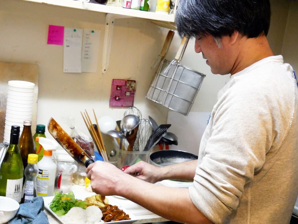 「~Diningめし屋~ふくちゃん」ハンバーグを盛り付ける店主の後ろ姿
