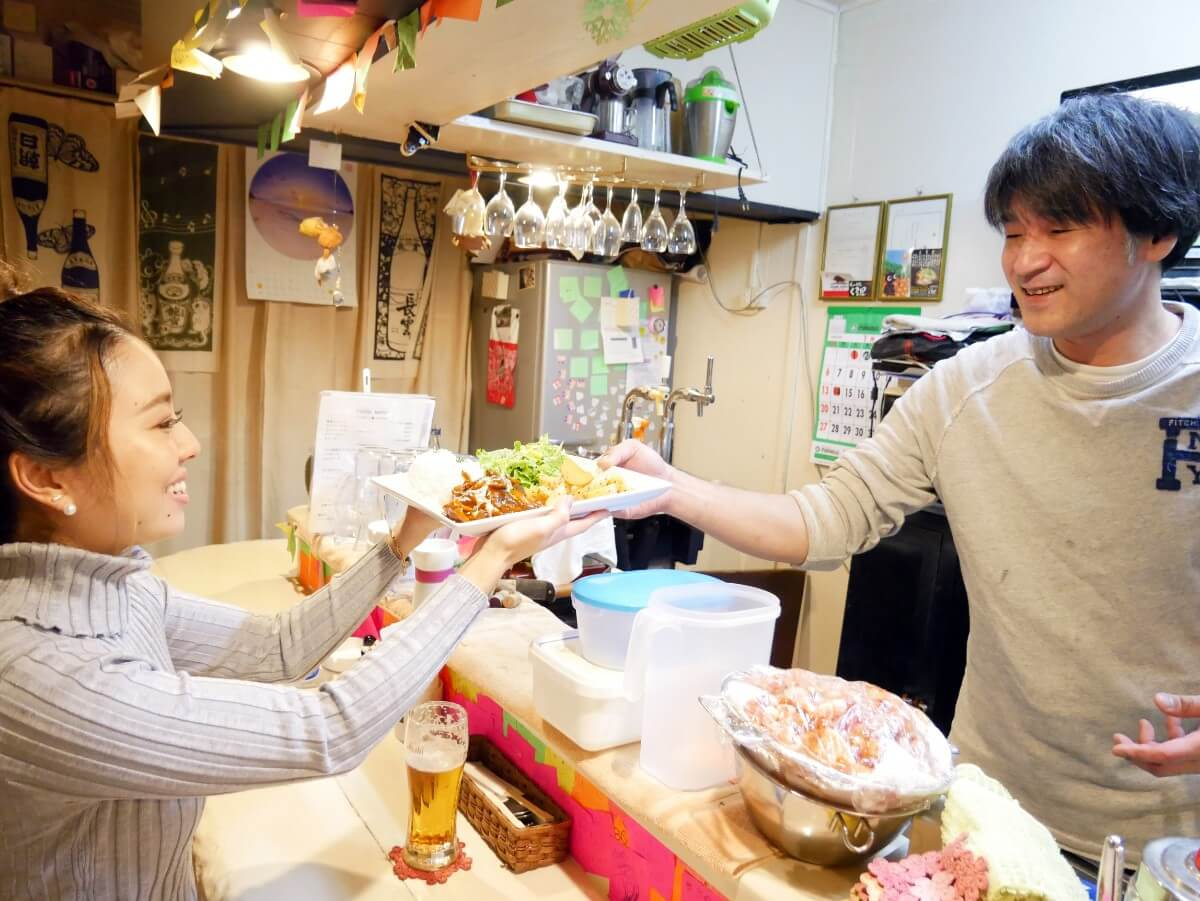 「~Diningめし屋~ふくちゃん」カウンター越しに料理を受け取る女性