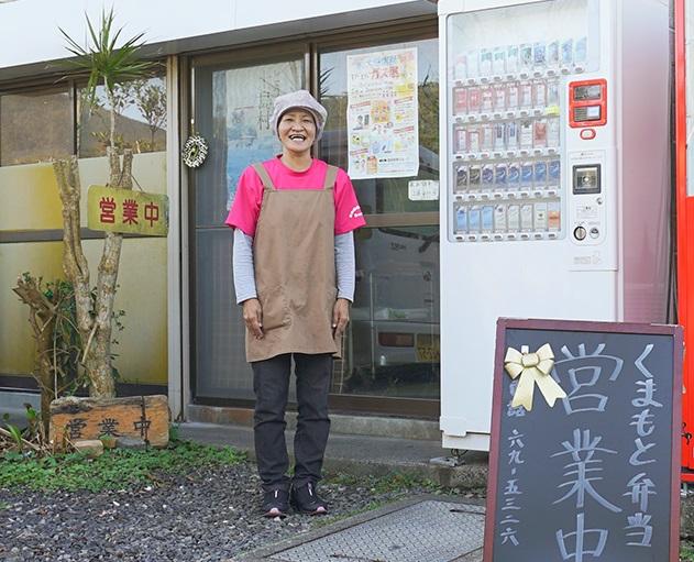 奄美住用くまもと弁当の店先に立つスタッフ