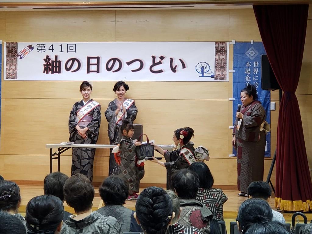 「紬の日のつどい」のお楽しみ抽選会で紬で作られたかばんを当てた女の子