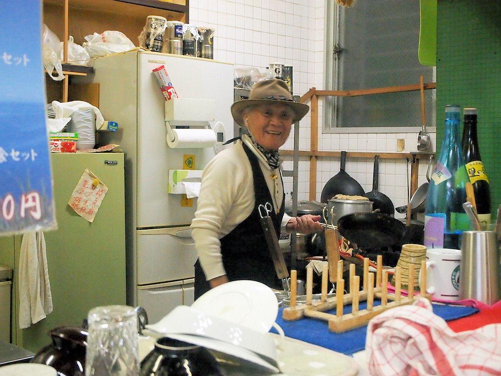 厨房で鍋を振る喫茶シャークの鮫島さん