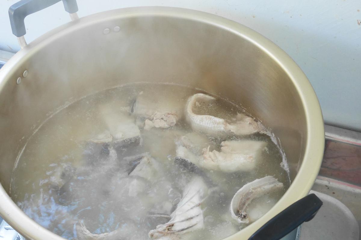 鍋で煮ている魚のアラ