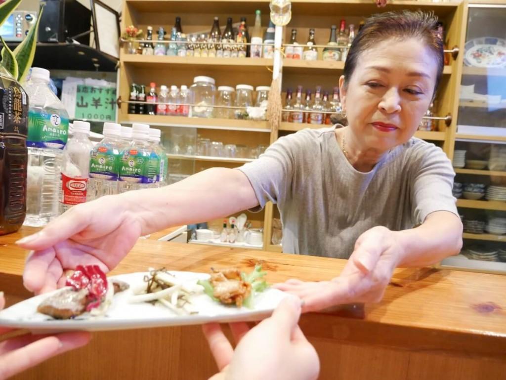 奄美屋仁川カウンター越しに料理を出す女性