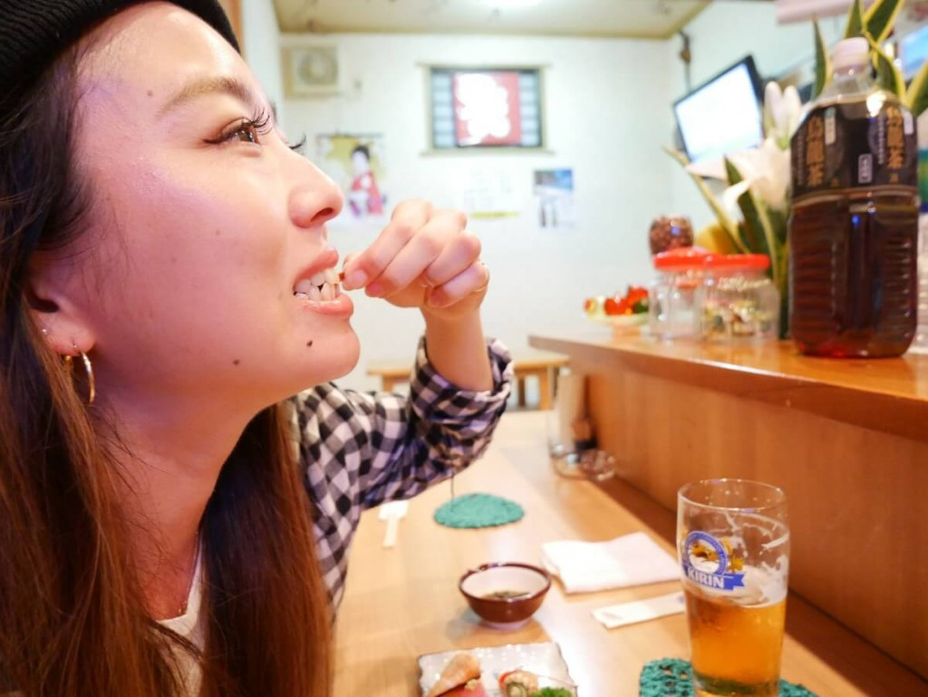 奄美屋仁川たんぽぽのカウンターで食事する女性
