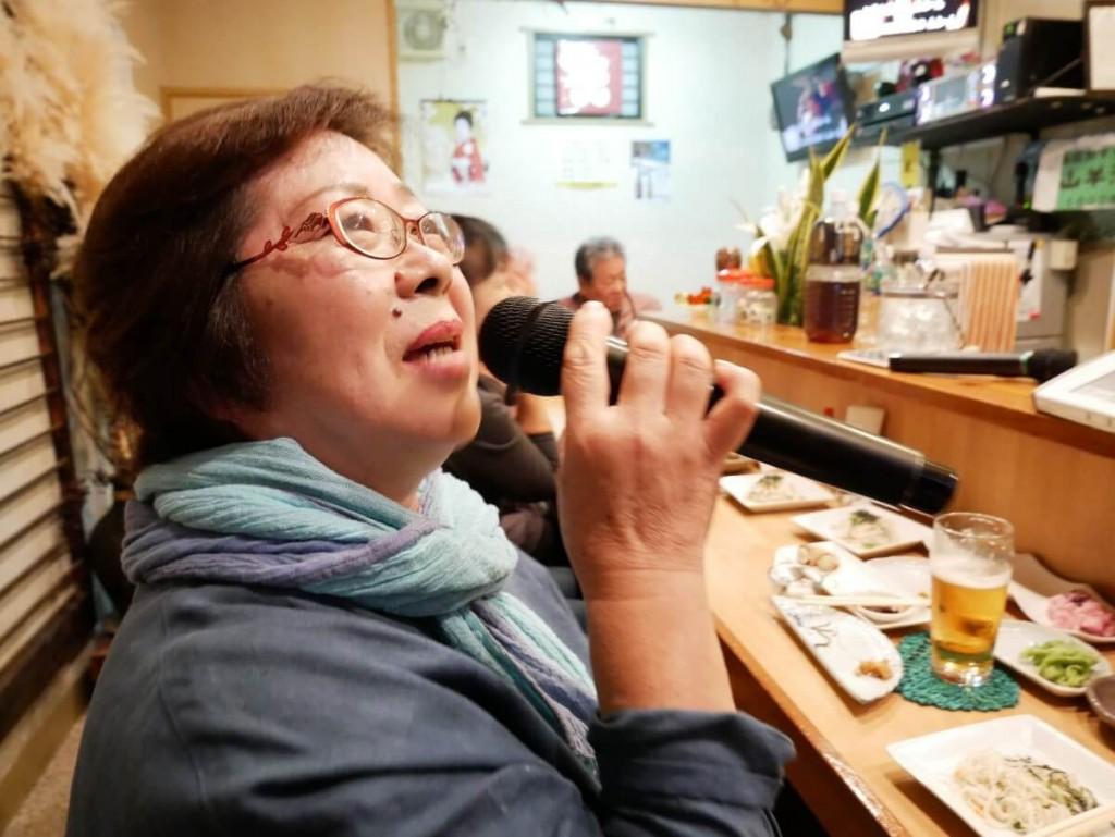 屋仁川のカウンターで歌う女性