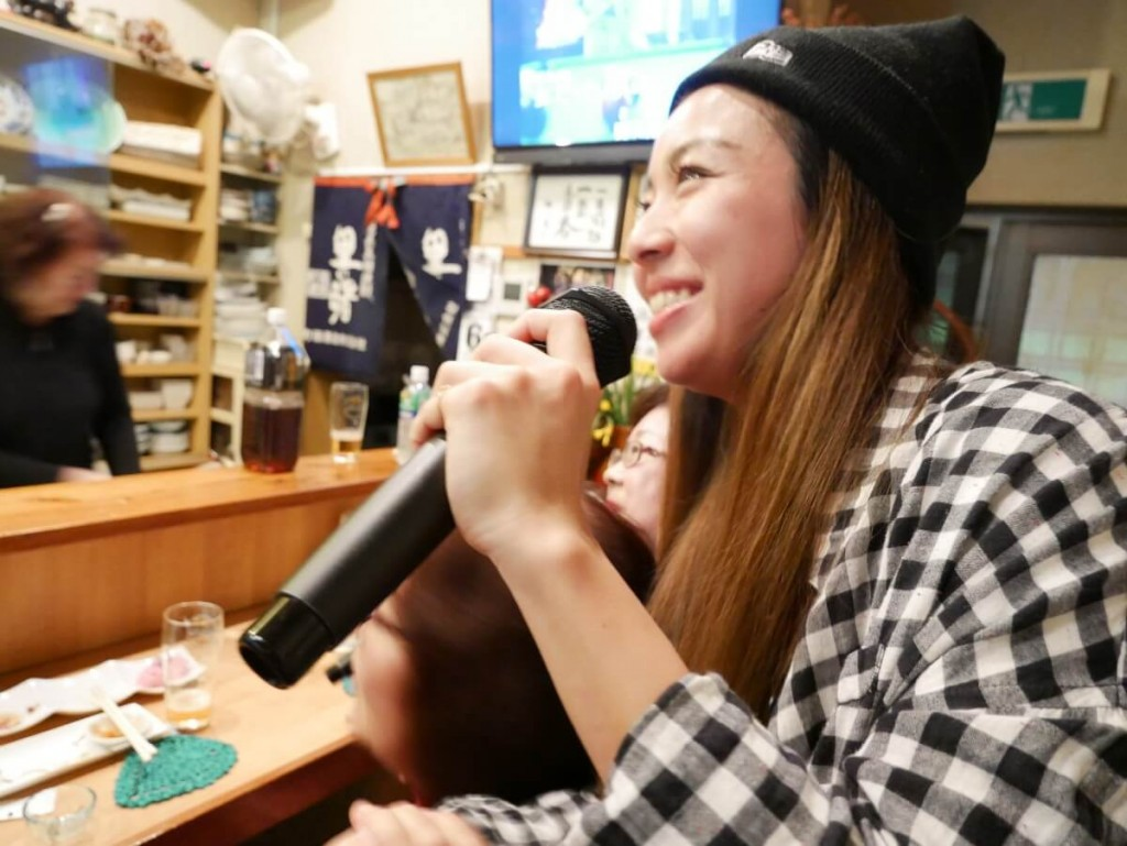 屋仁川の小料理屋でカラオケをする女性