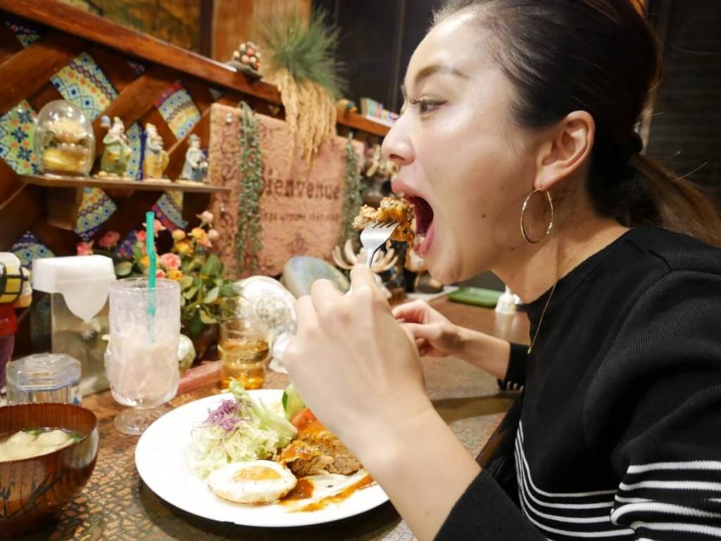 喫茶店でハンバーグを食べる女性