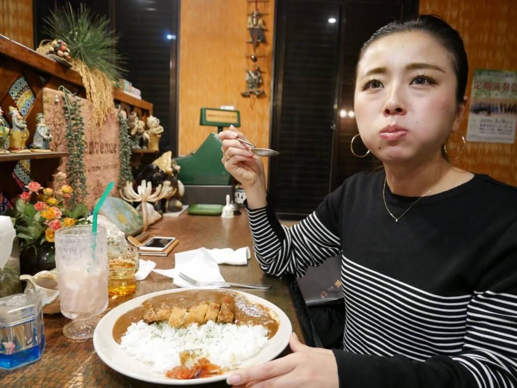 喫茶店でカツカレーを食べる女性
