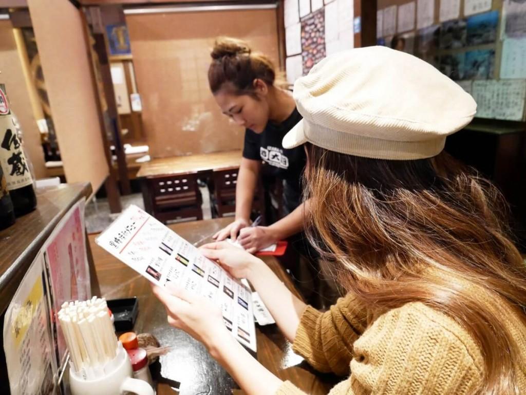 居酒屋のカウンターで注文する女性
